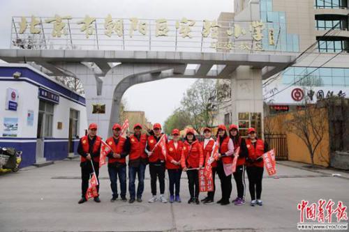 """北京市朝阳区实验小学雄安校区,参加""""家校警""""护学队的当地家长志愿者在校门口。"""
