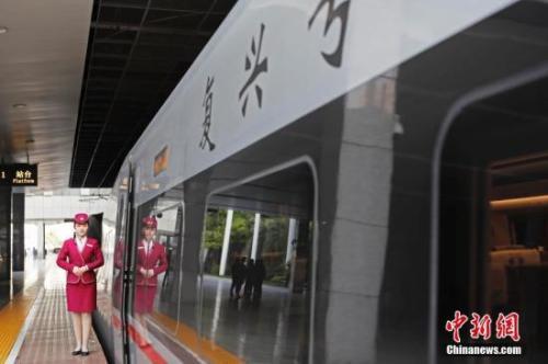 """资料图:4月10日,列车员在""""复兴号""""列车旁迎接旅客的到来。 <a target='_blank' href='http://www.chinanews.com/'>中新社</a>记者 殷立勤 摄"""
