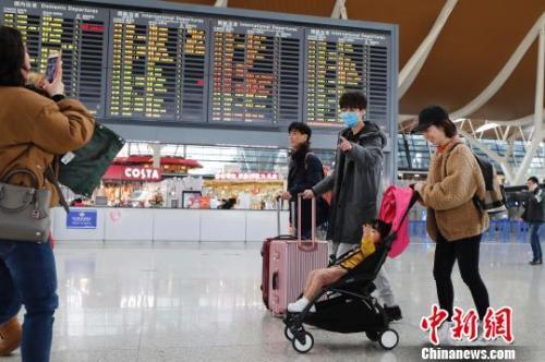 旅客带着孩子前往办票柜台办理登机手续。 殷立勤 摄